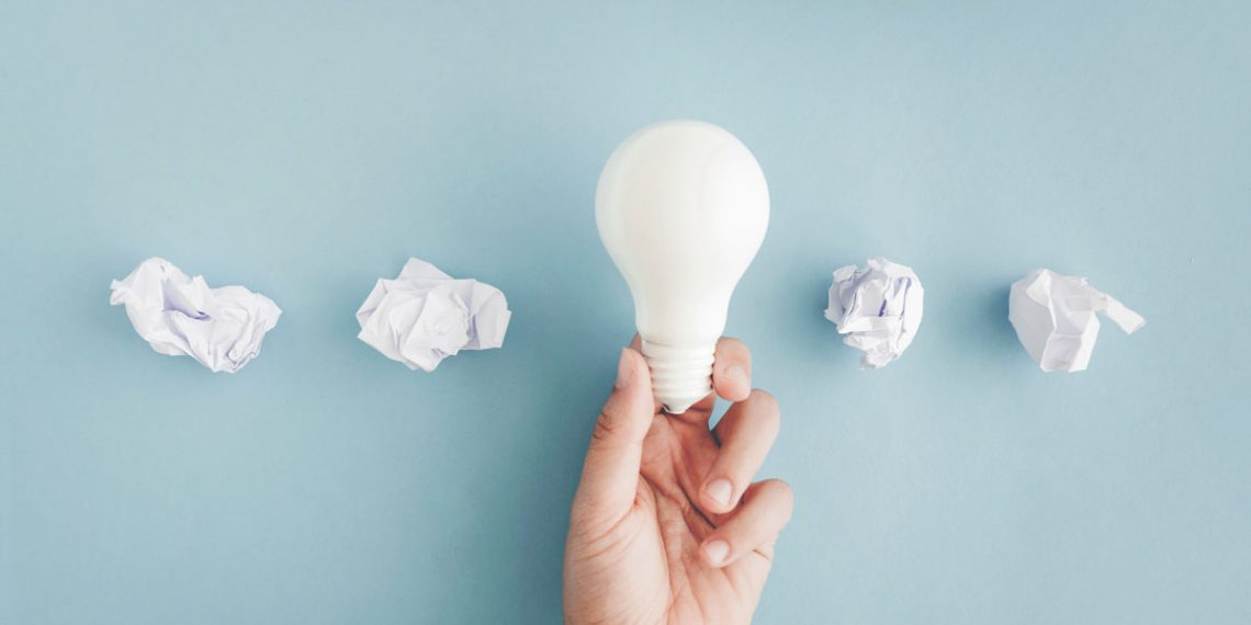 Hand holding white light bulb with crumpled paper balls on gray background photo